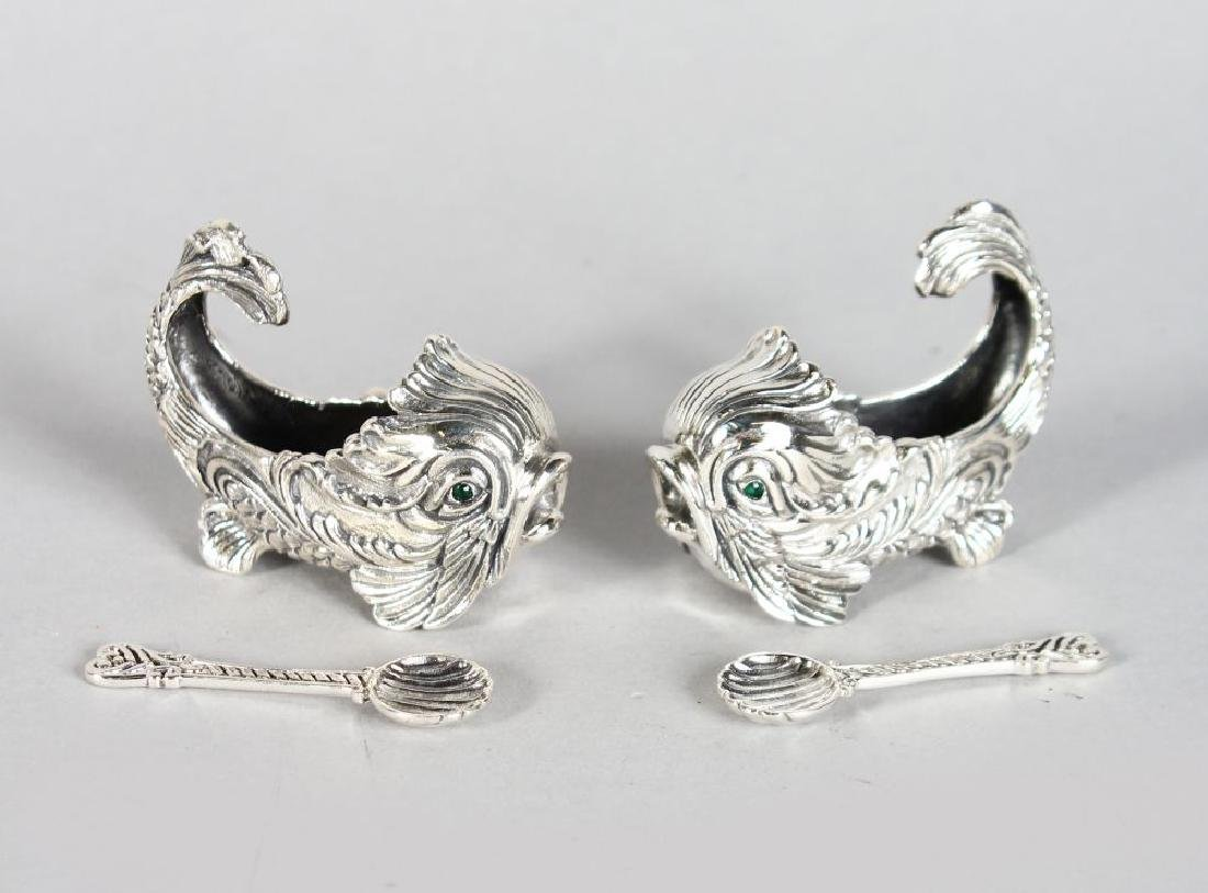 A GOOD PAIR OF SILVER DOLPHIN SHAPED SALTS AND SPOONS.