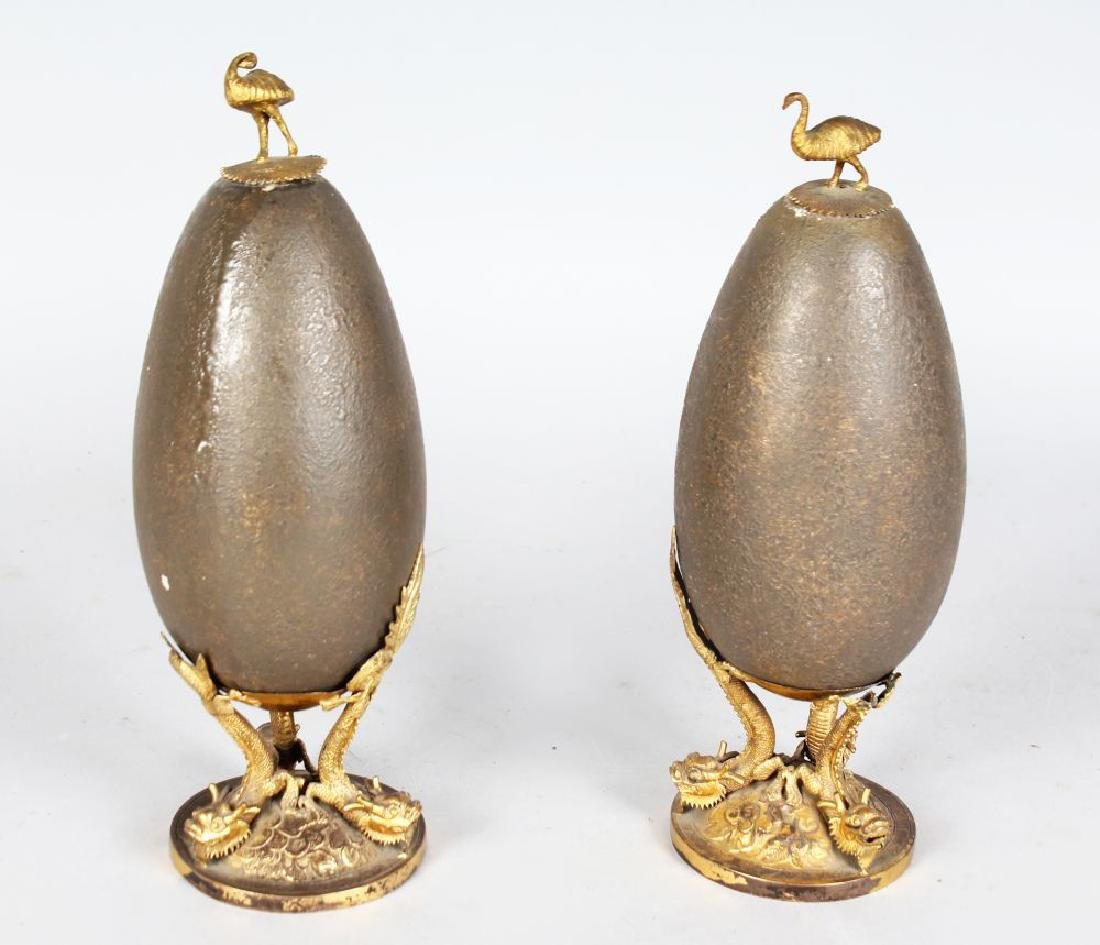 A PAIR OF ORMOLU MOUNTED EMU EGGS, the top with an emu,