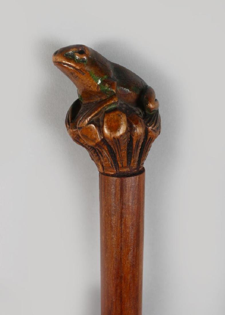 A FOLK ART WALKING STICK with carved frog handle.