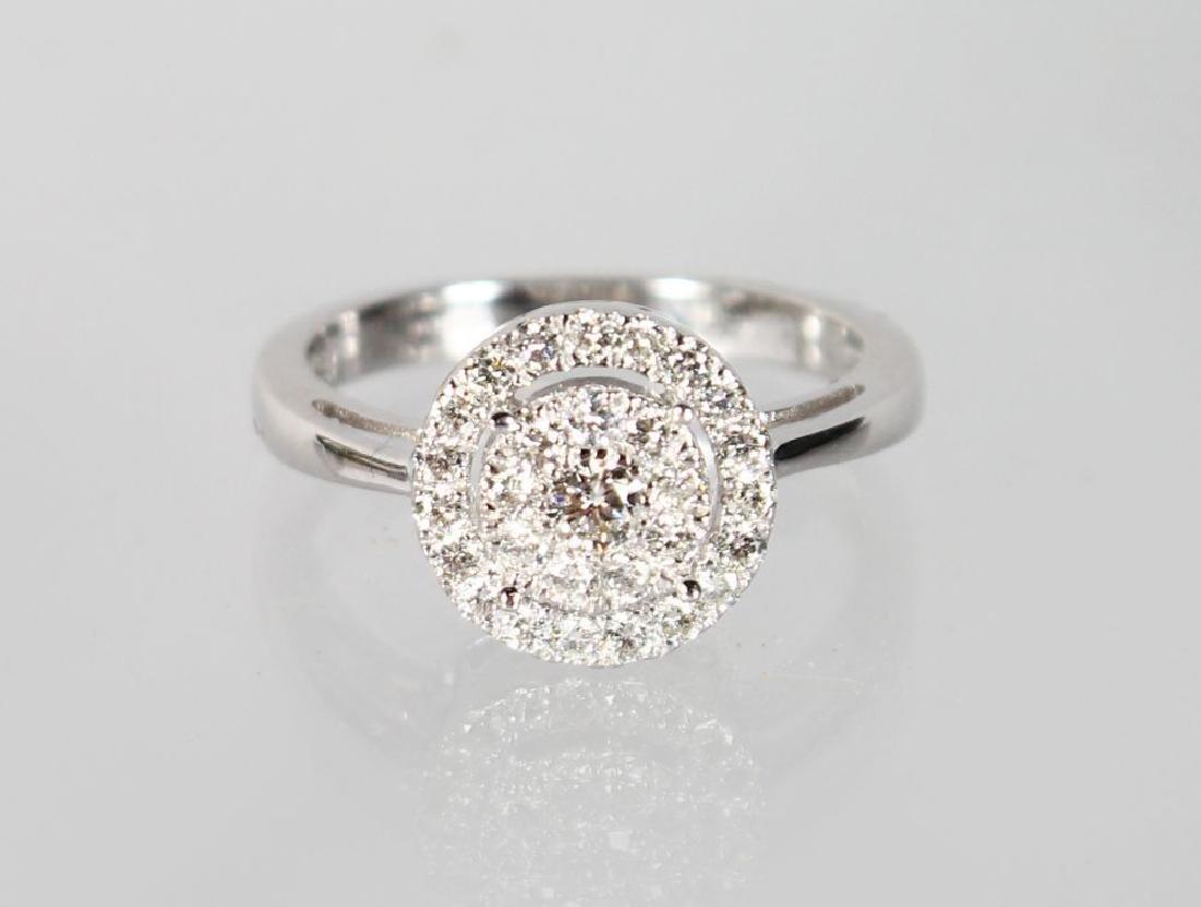 A 9CT GOLD CIRCULAR DIAMOND CLUSTER RING.