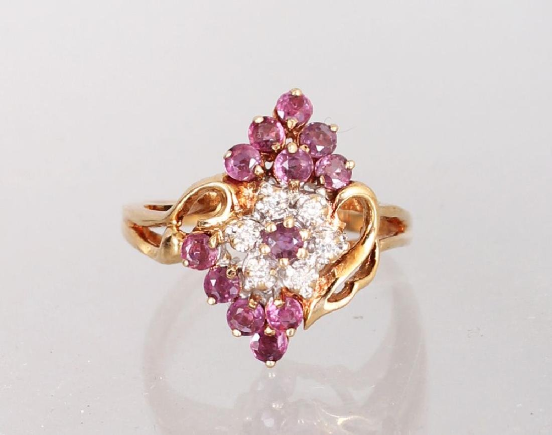 A 10K YELLOW GOLD, DIAMOND AND RUBY CLUSTER RING.