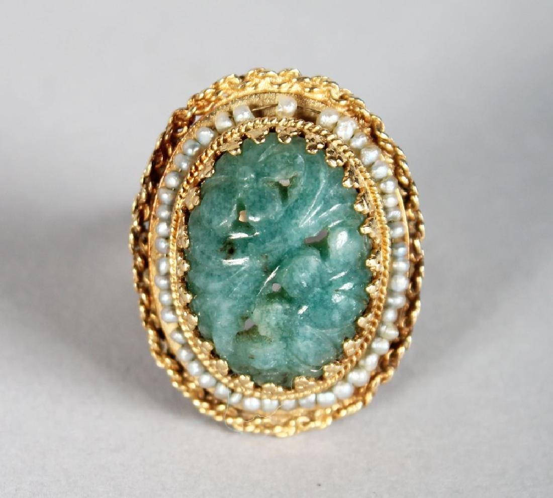 A GOLD AND JADE RING, the oval jade stone with carved