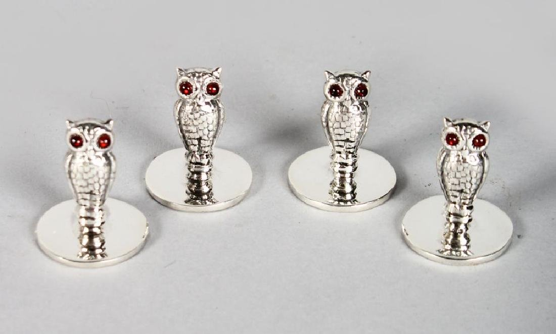 A SET OF FOUR SILVER OWL MENU HOLDERS.