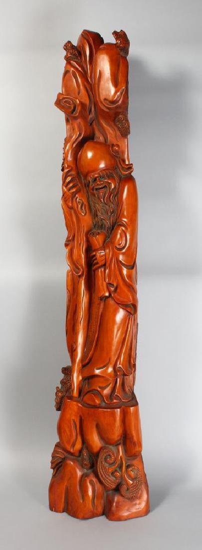A LARGE CHINESE CARVED WOOD FIGURE, standing 4ft 6ins.