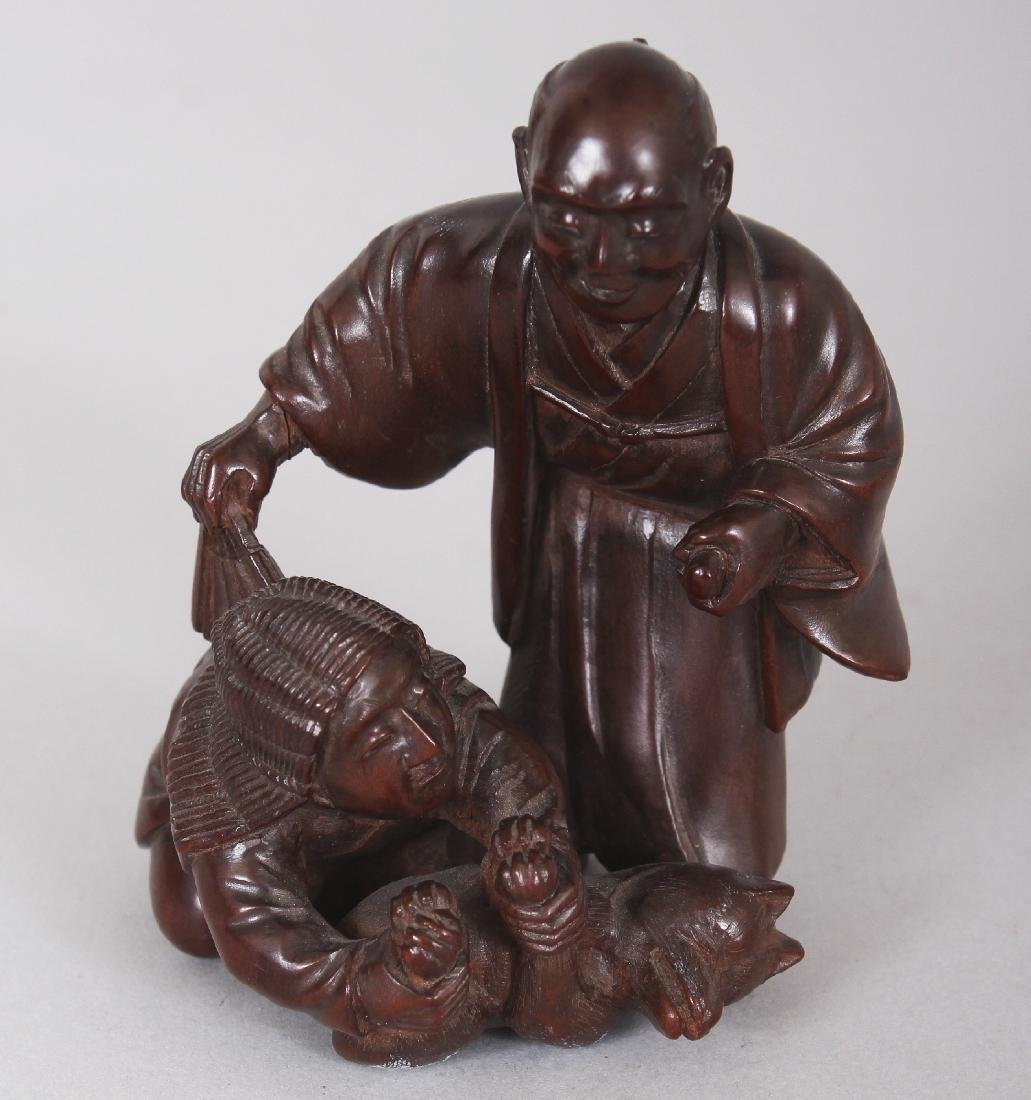 A JAPANESE CARVED WOOD GROUP OF TWO MEN & A FOX, one of