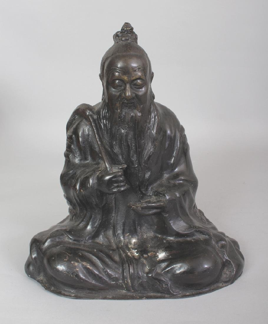 A CHINESE BRONZE FIGURE OF A SEATED SAGE, bearing a fly