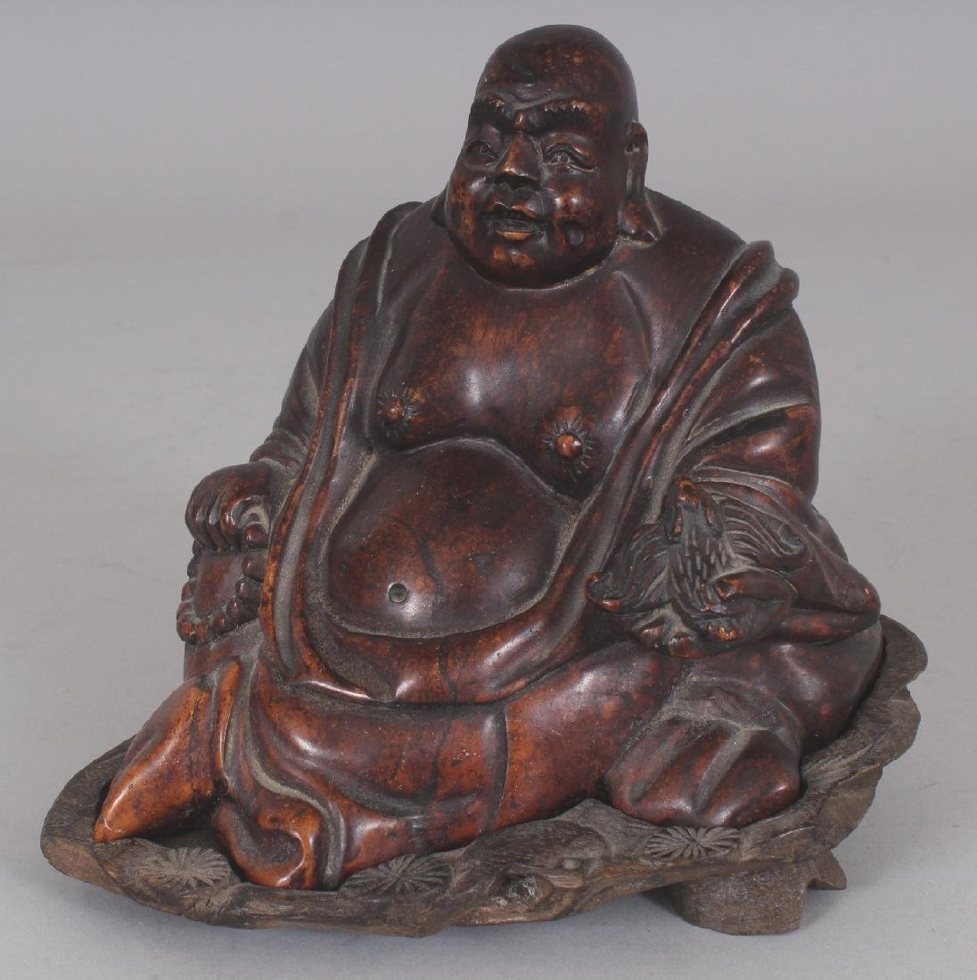 A 20TH CENTURY CHINESE BROWN STONE CARVING OF BUDAI,
