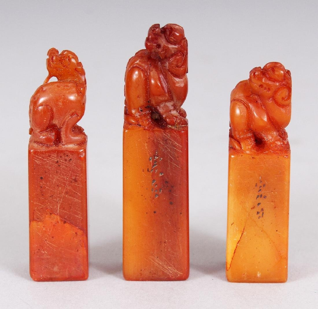 A CHINESE WOOD CASED SET OF THREE SMALL STONE SEALS,