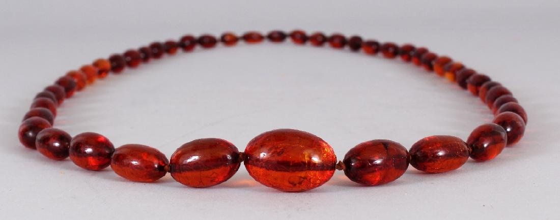AN AMBER NECKLACE, weighing approx. 80.5gm, composed of - 2