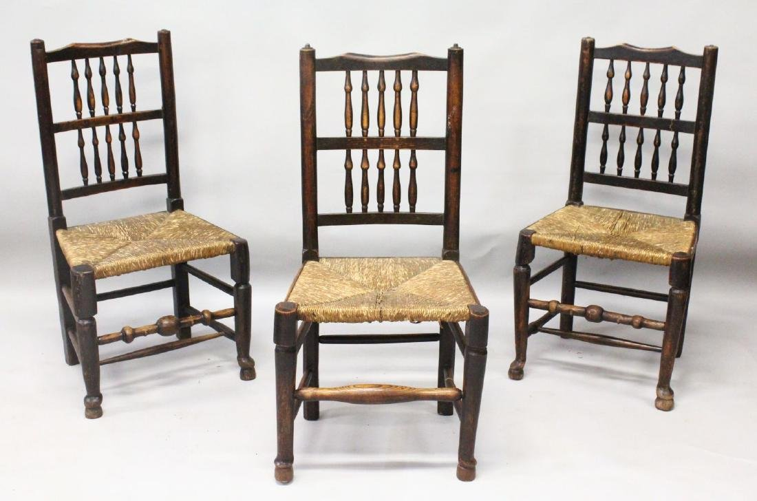 A SET OF THREE ELM SPINDLE BACK SINGLE CHAIRS with rush