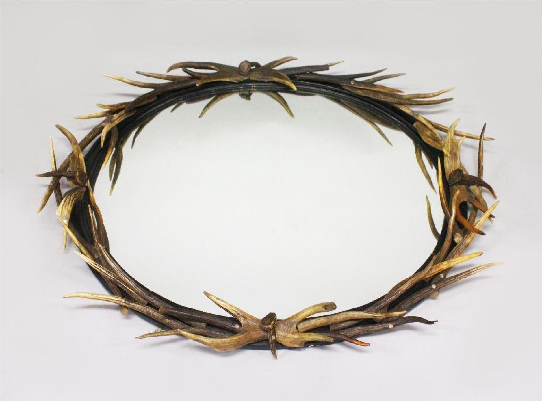 A LARGE ANTLER OVAL MIRROR, the frame entwined with