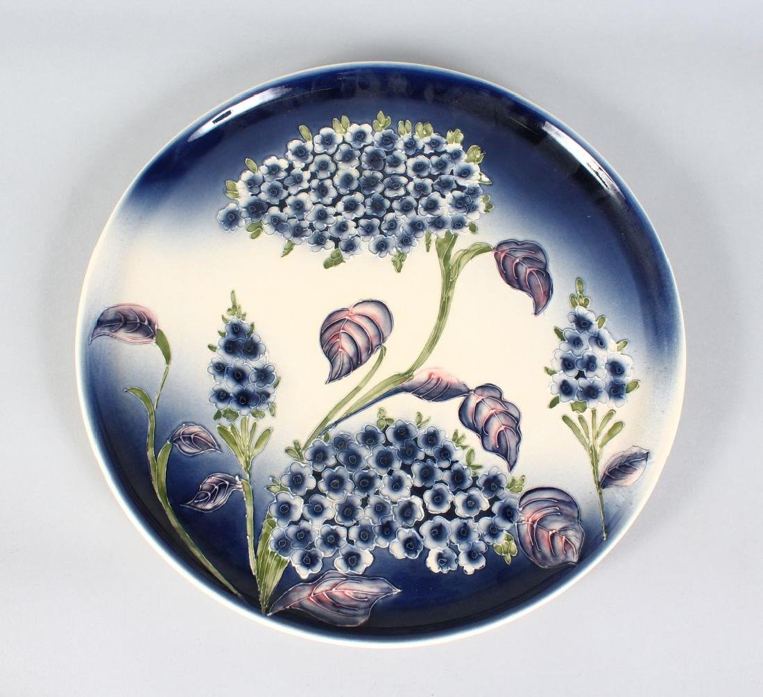 A MOORCROFT STYLE CIRCULAR PORCELAIN CHARGER.  14ins