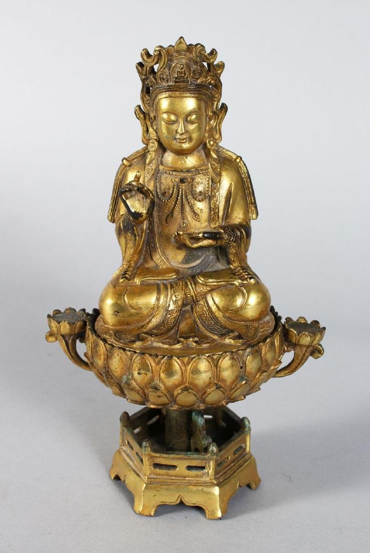 A CHINESE GILT BRONZE DEITY on a stand.  10ins high.