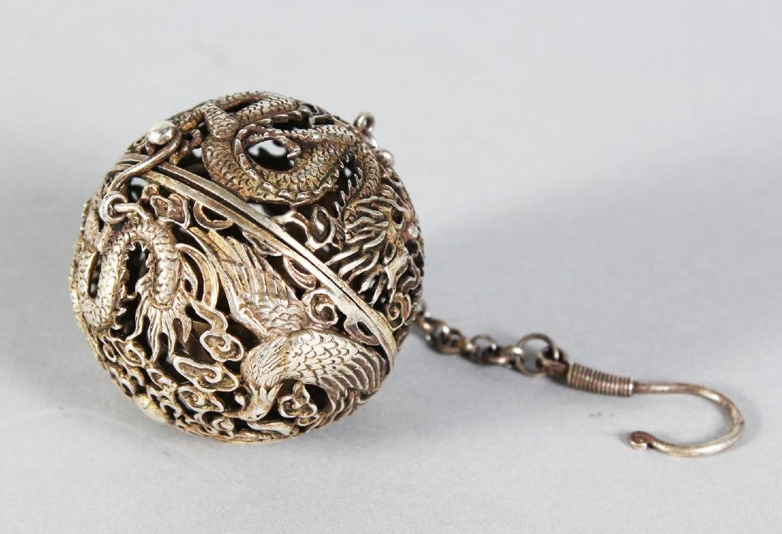 A PIERCED SILVER TRAVELLING CENSER on a chain.