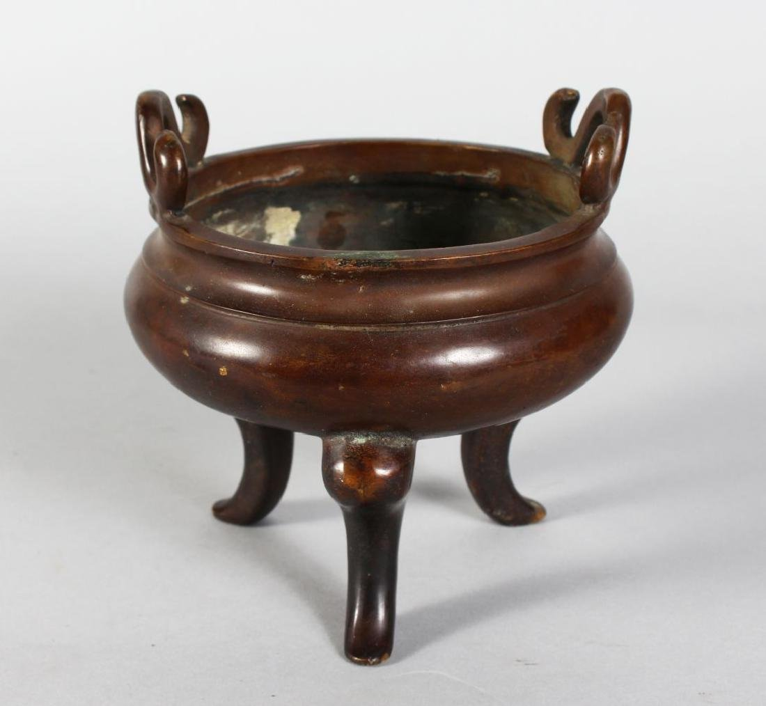 A CHINESE CIRCULAR BRONZE TWO HANDLED CENSER on three
