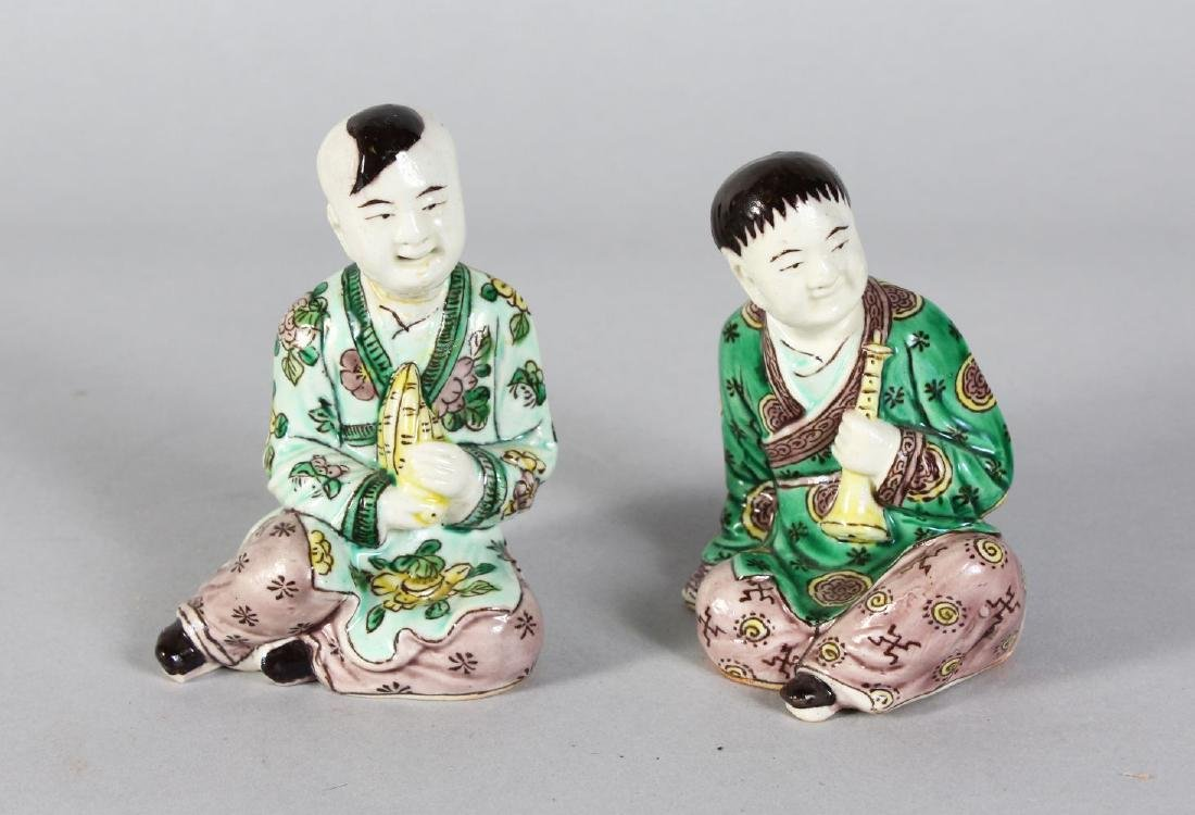 TWO SMALL FAMILLE ROSE PORCELAIN SEATED FIGURES. 5ins