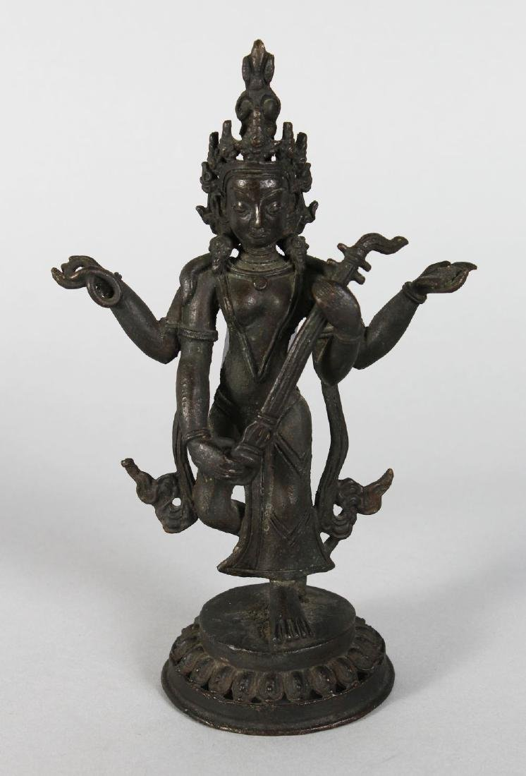 A SMALL CHINESE GILT BRONZE DEITY with four arms. 8ins