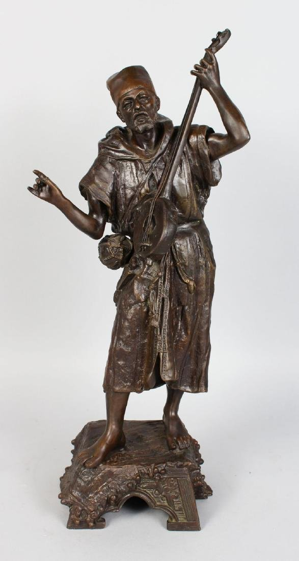 A LARGE AUSTRIAN BRONZE OF A MAN PLAYING A MUSICAL
