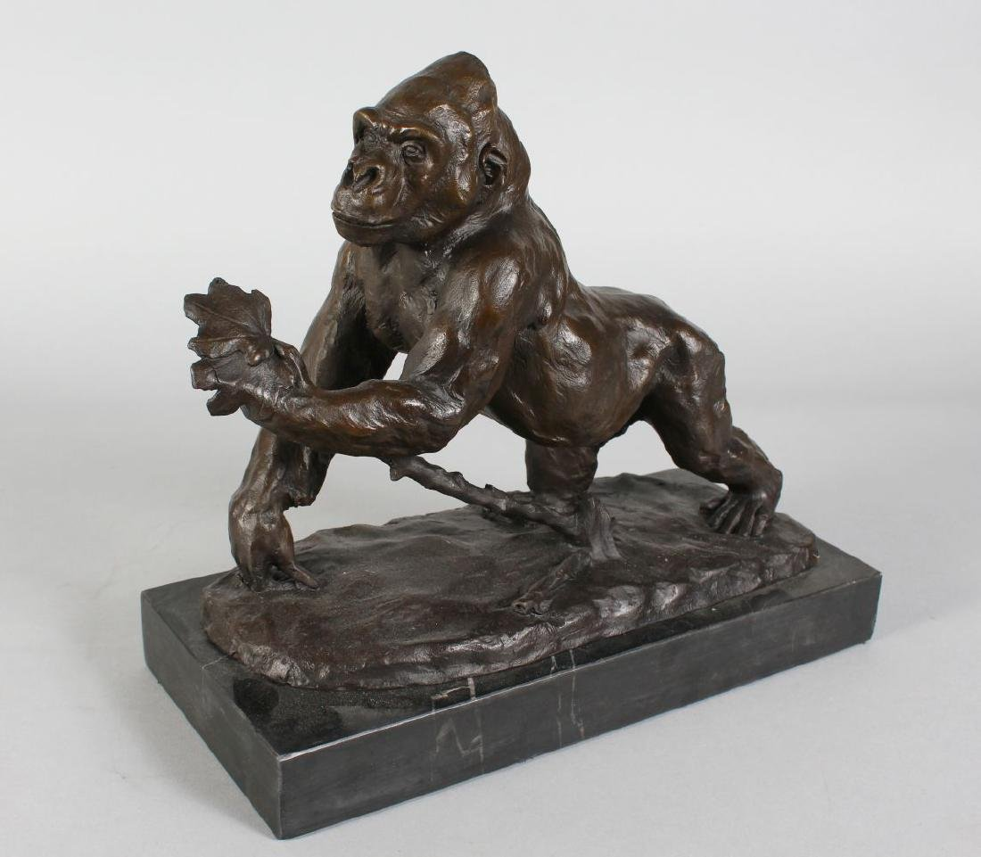 A BRONZE OF A GORILLA  on a rectangular marble base.