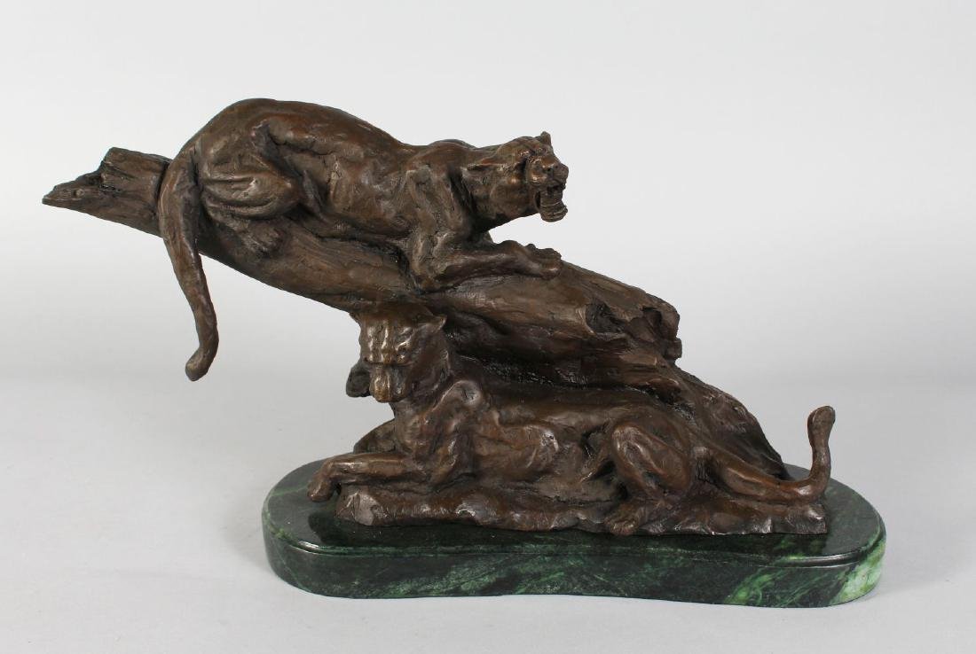 A BRONZE OF TWO TIGERS on a rock.  Signed, on an oval