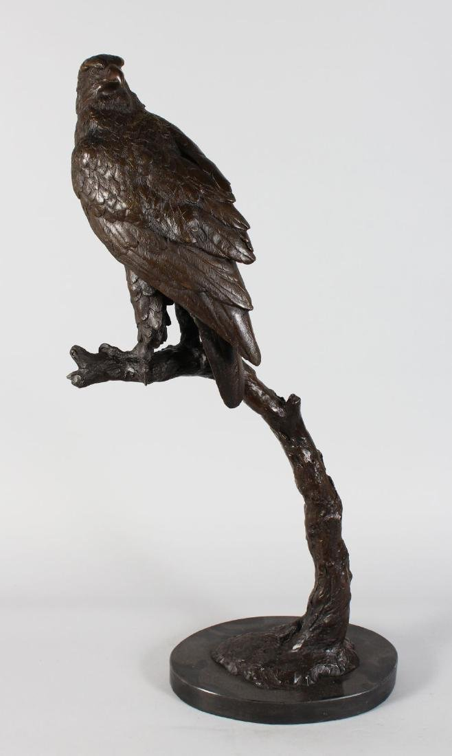 A LARGE BRONZE OF A BIRD OF PREY ON A BRANCH  standing