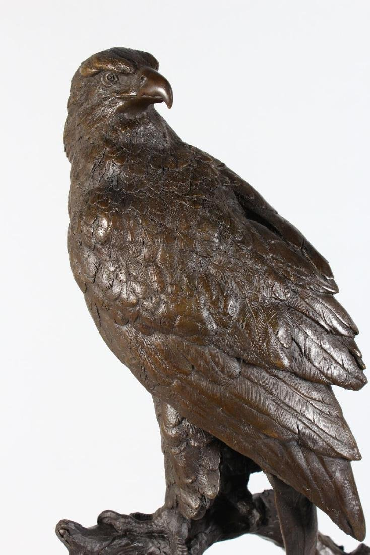 A LARGE BRONZE OF A BIRD OF PREY ON A BRANCH  standing - 2