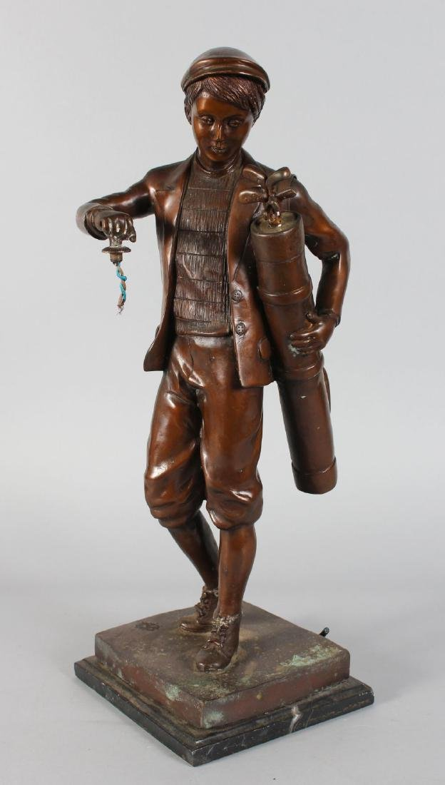 A  BRONZE OF A YOUNG GOLFER carrying a bag of golf