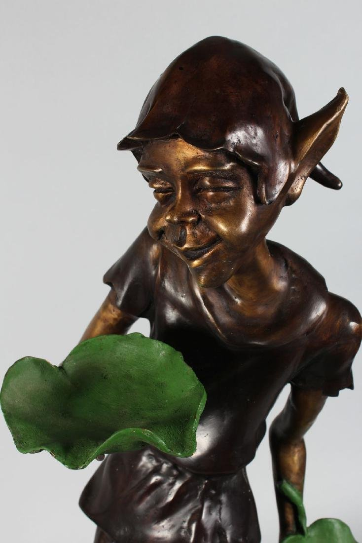 A TWO COLOUR BRONZE PIXIE holding two leaves.  31ins - 2