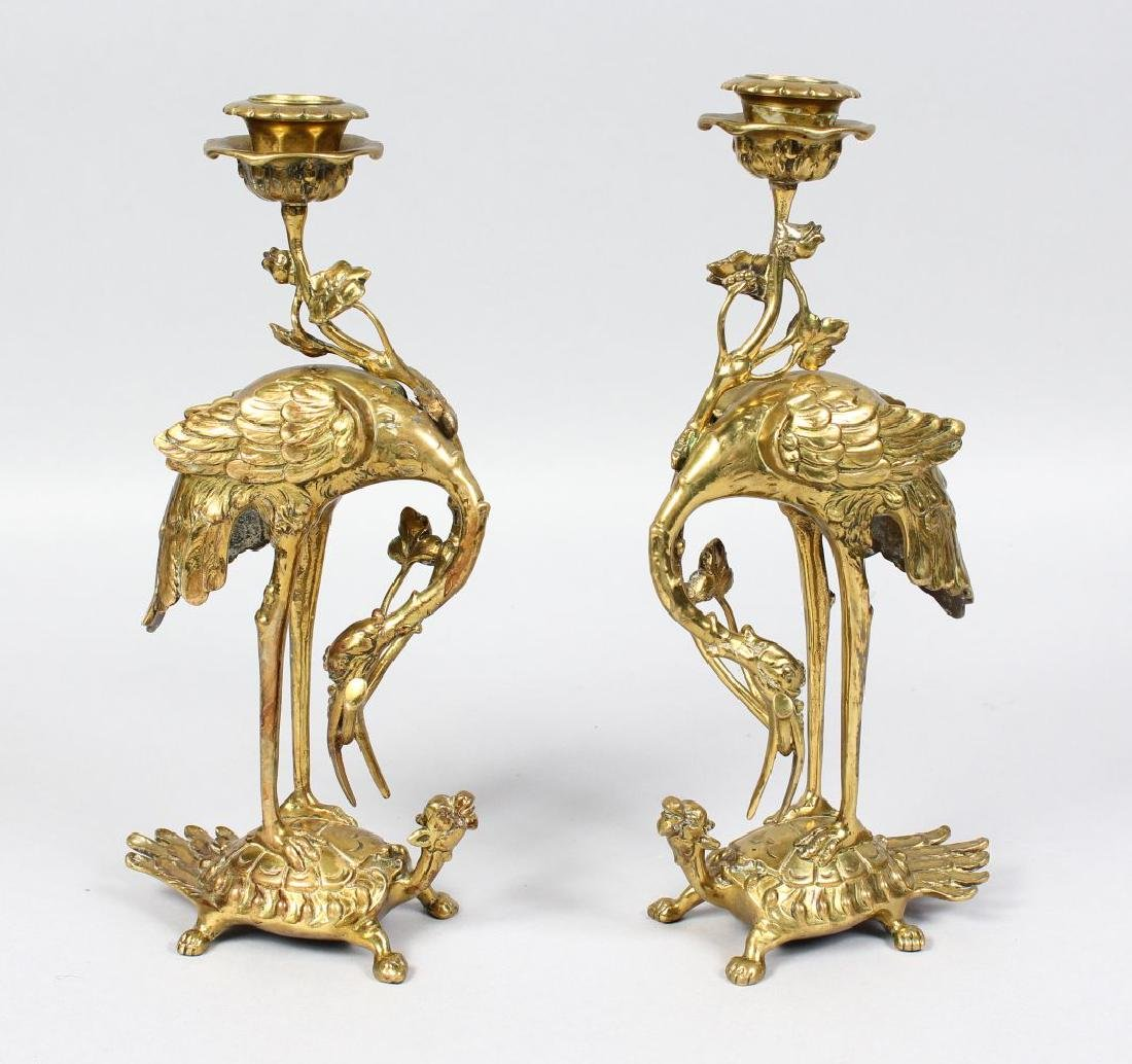 A PAIR OF BRASS STANDING STORK CANDLESTICKS, standing