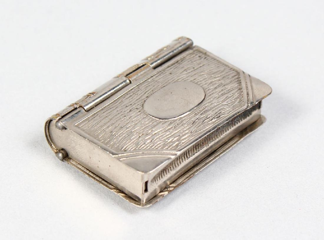A BOOK SHAPED VESTA AND STAMP BOX COMBINED.