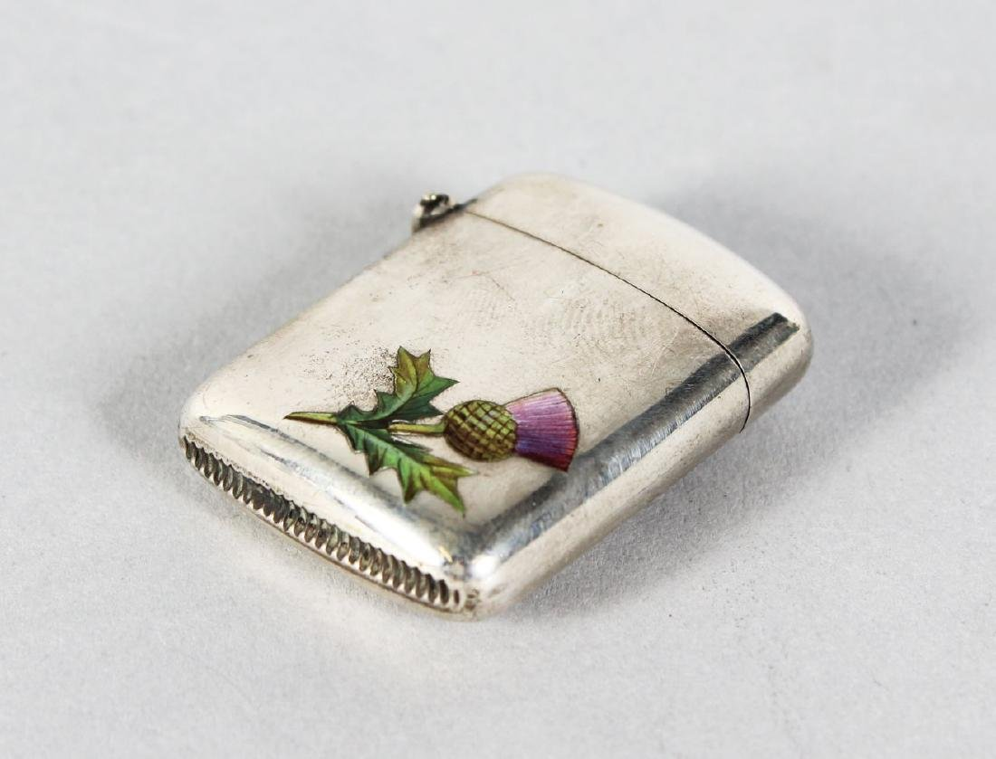 A VICTORIAN SILVER VESTA with an enamel thistle.