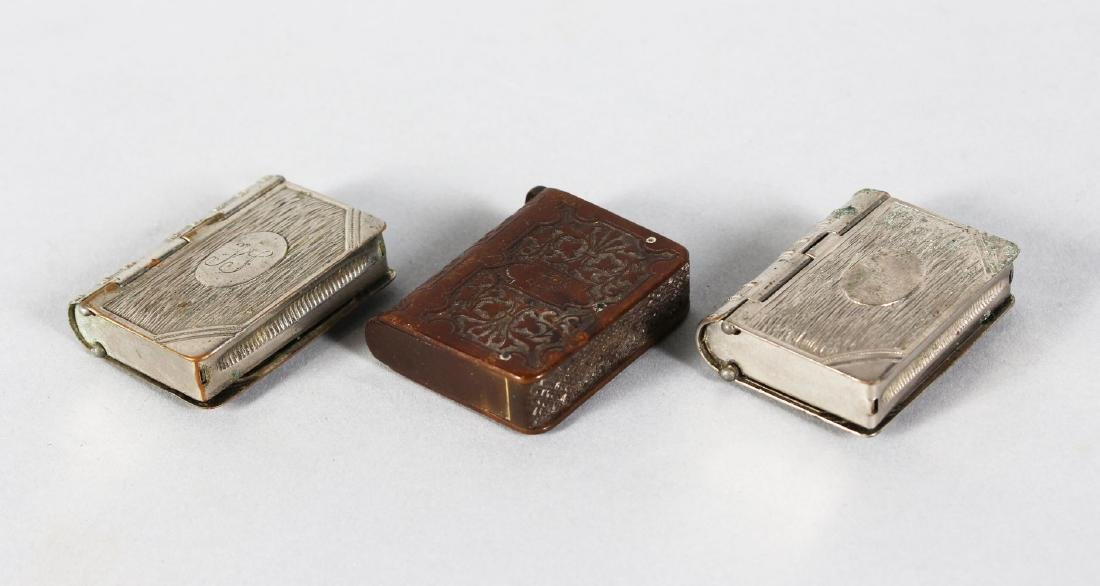 A VULCANITE BOOK SHAPED VESTA and TWO PLATED BOOK