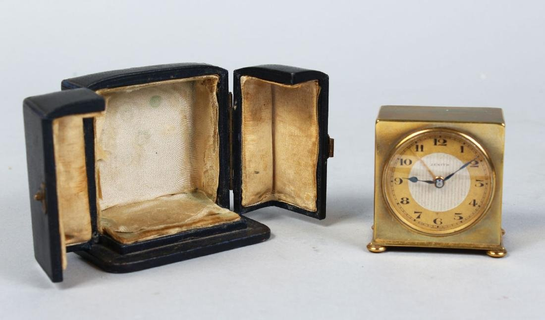 A MINIATURE TRAVELLING CLOCK in a folding leather case.