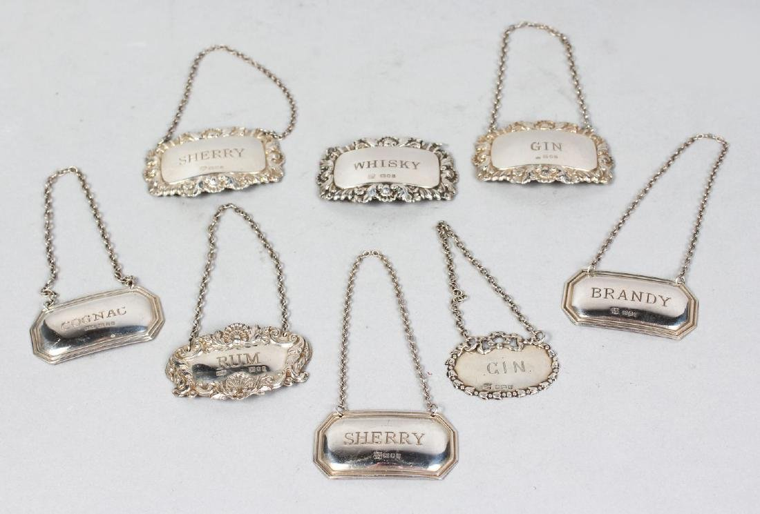 EIGHT VARIOUS SILVER DECANTER LABELS.