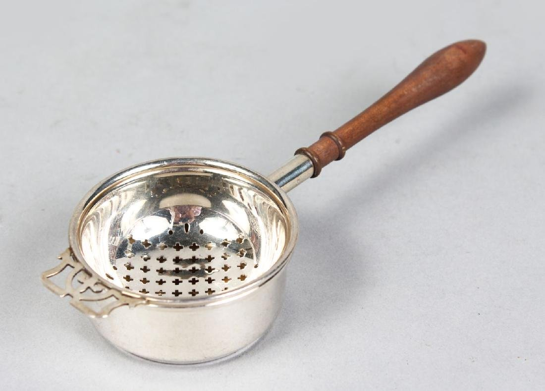 A SMALL SILVER TEA STRAINER AND STAND.