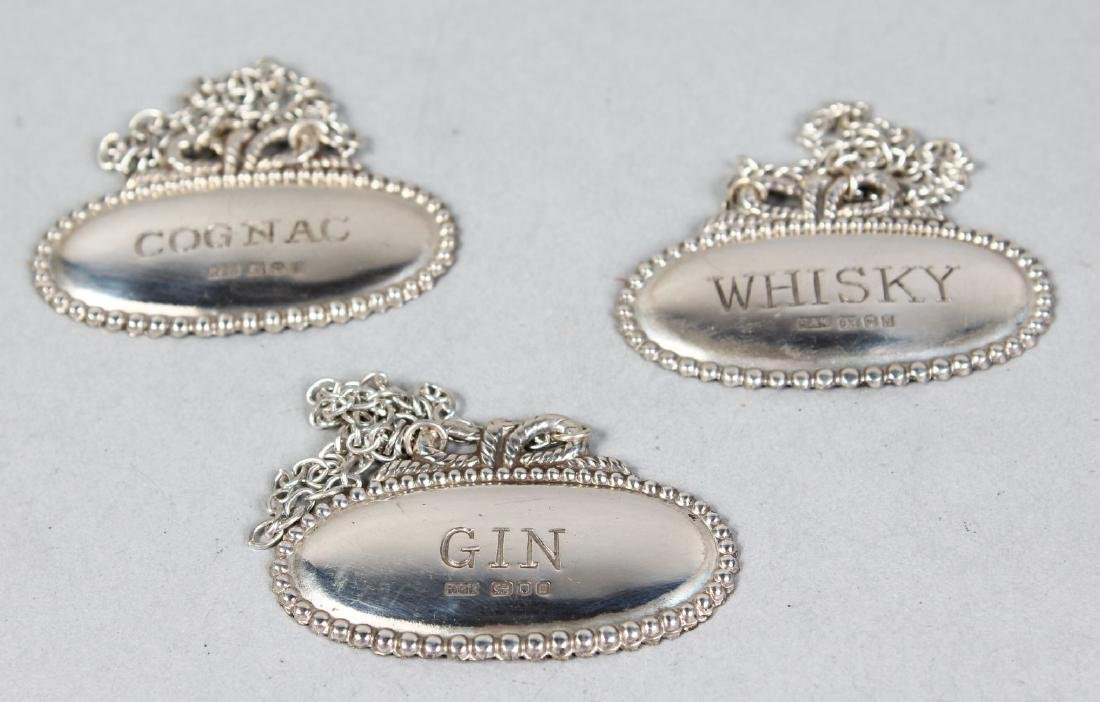 THREE SILVER DECANTER LABELS, Whisky, Cognac and Gin.