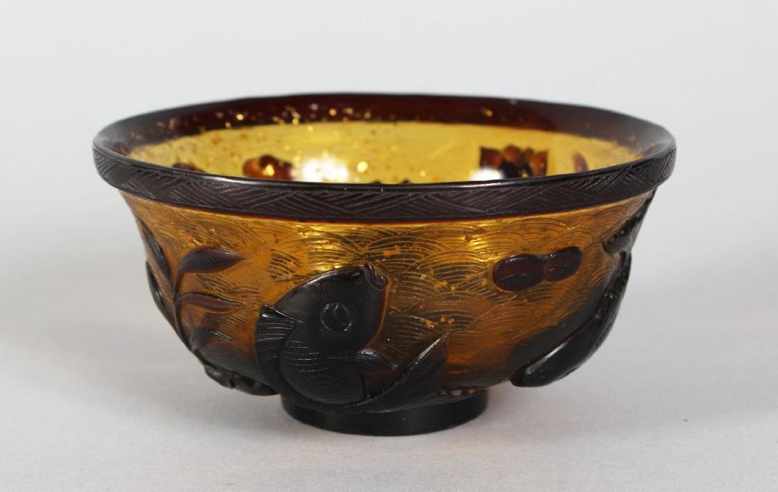 A PEKING GLASS BOWL decorated with fish in relief.