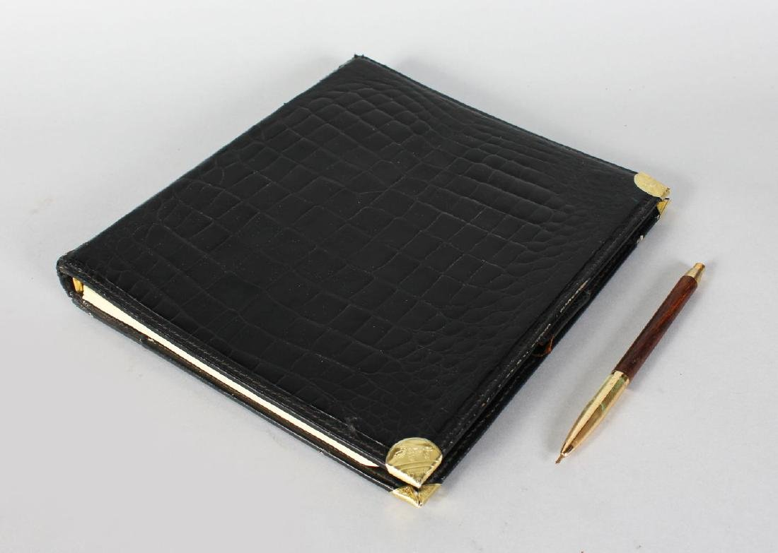 A GUCCI BLACK CROCODILE NOTE PAD.