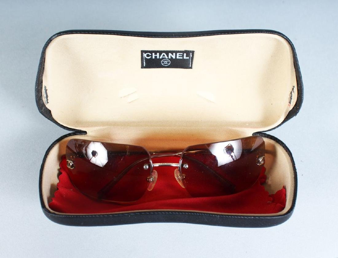 A PAIR OF CHANEL SUNGLASSES, in a folding case.