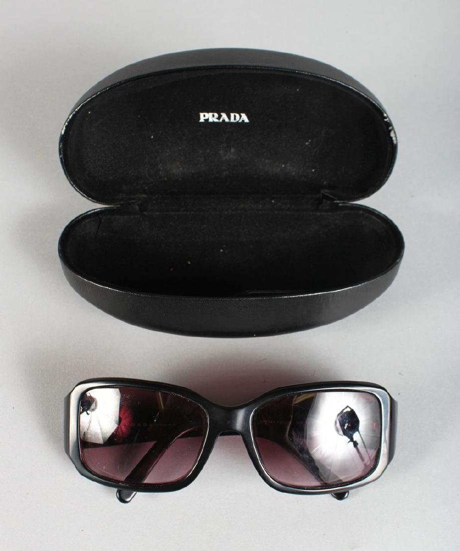 A PAIR OF PRADA SUNGLASSES, in a folding case..