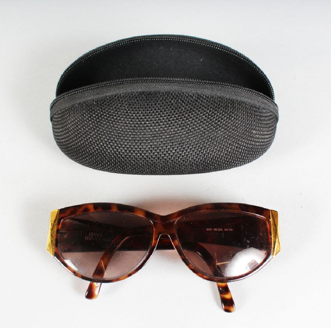 A PAIR OF PERCY SUNGLASSES, in a folding case.