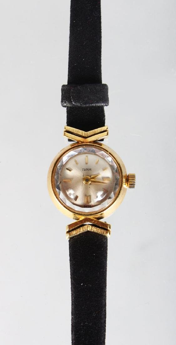A LADIES TUDOR GOLD WRISTWATCH with leather strap.