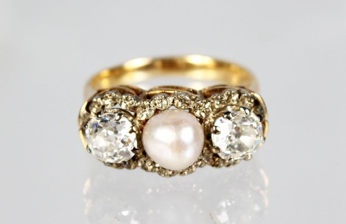 A TWO STONE DIAMOND AND PEARL RING.