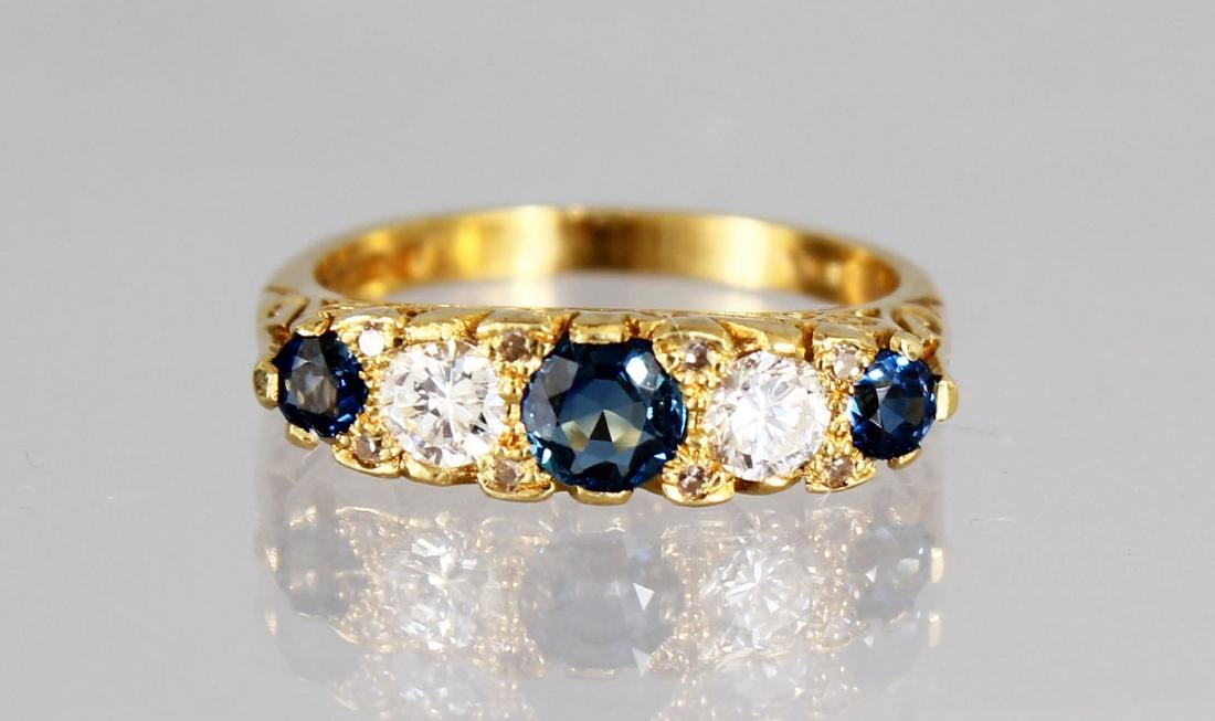 AN 18CT GOLD FIVE STONE DIAMOND AND SAPPHIRE RING.