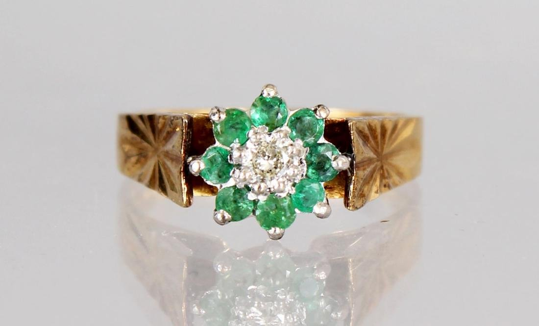AN 18CT GOLD, EMERALD AND DIAMOND CLUSTER RING.