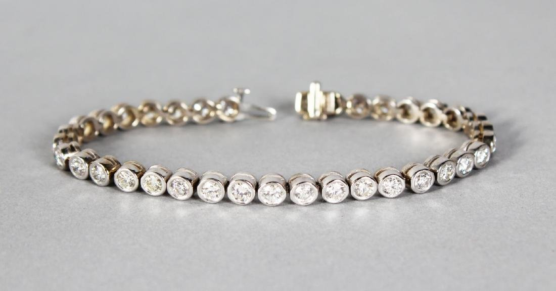 A 14CT WHITE GOLD DIAMOND COLLET SET LINE BRACELET OF