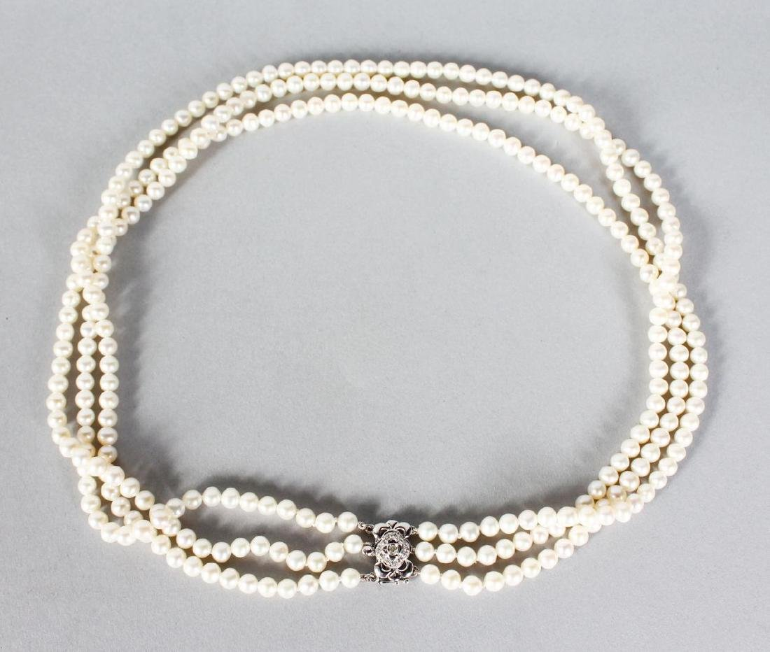 A THREE ROW CULTURED PEARL NECKLACE with white gold and