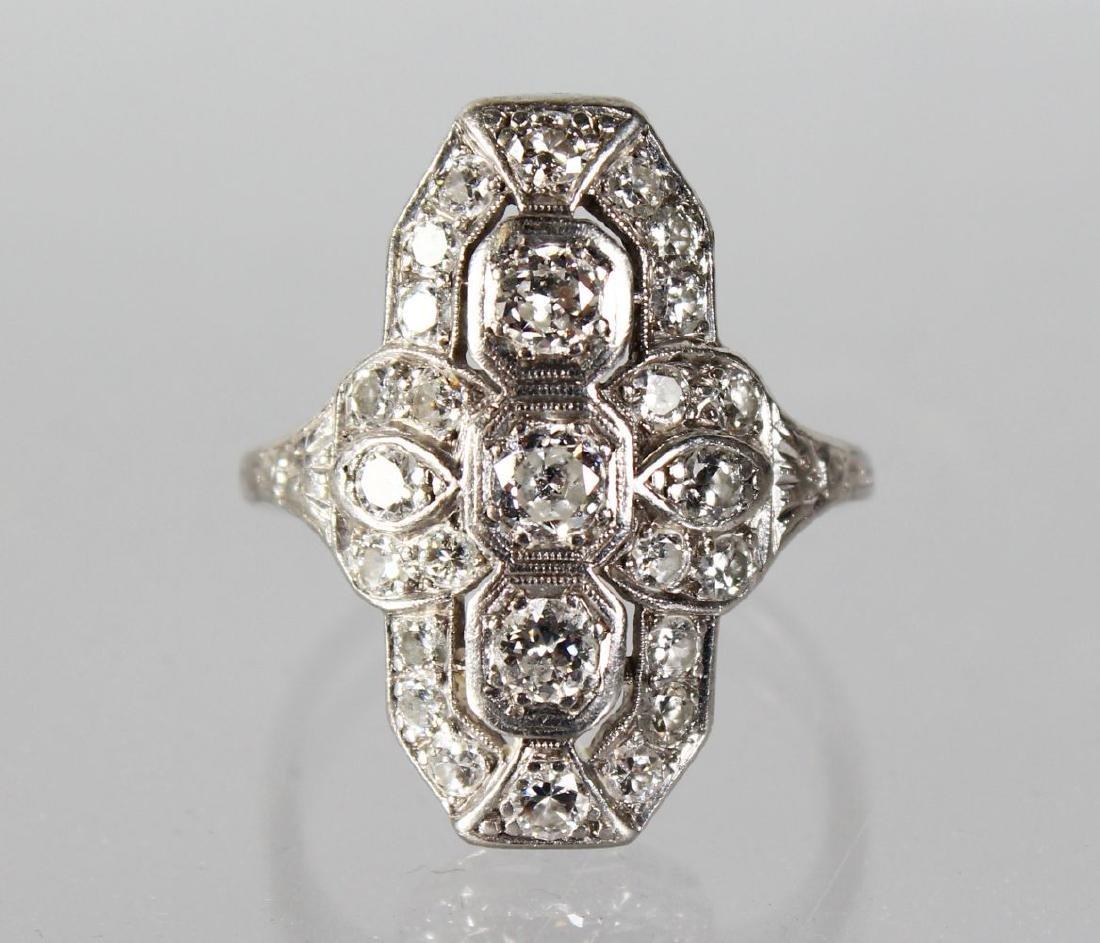 AN ART DECO DIAMOND RING with three diamonds.