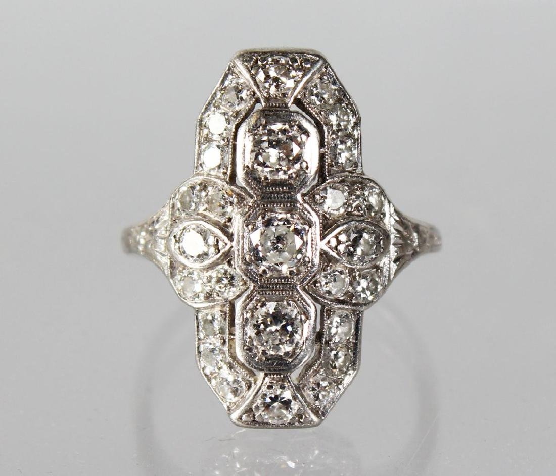 AN ART DECO DIAMOND RING with three diamonds.