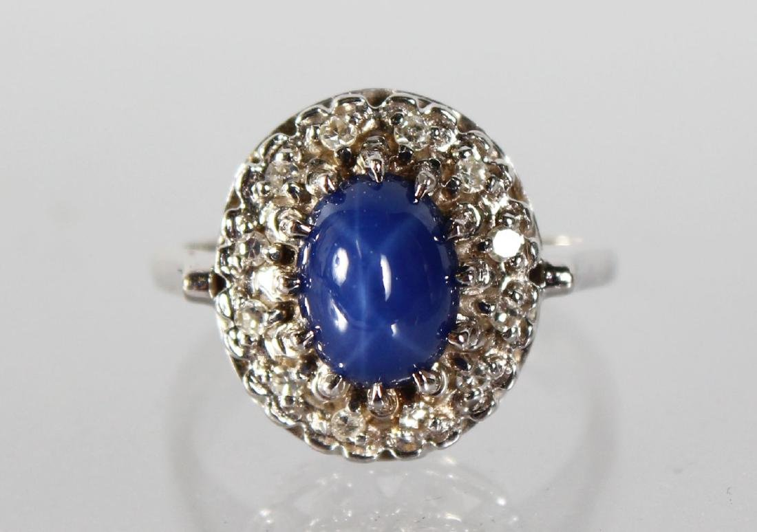 A CABOUCHON SAPPHIRE AND DIAMOND CLUSTER RING.